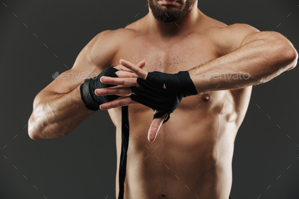Close up of a healthy muscular man tying boxing bandages - Stock Photo - Images