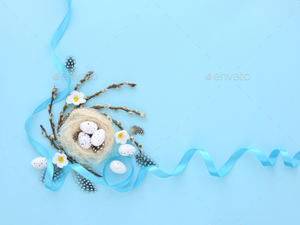 Easter egg in nest and willow branches on blue background. Easte - Stock Photo - Images