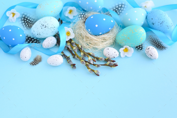 Easter eggs and and willow branches on blue background. Easter c - Stock Photo - Images