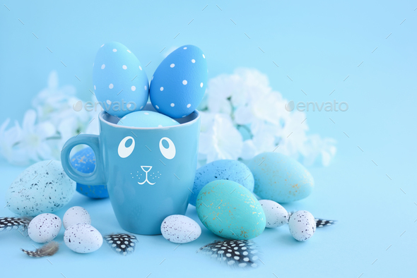 Easter eggs and a cup in the form of a rabbit on a blue backgrou - Stock Photo - Images