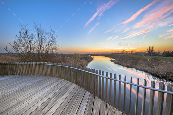 Planking balustrade sunset over swamp - Stock Photo - Images