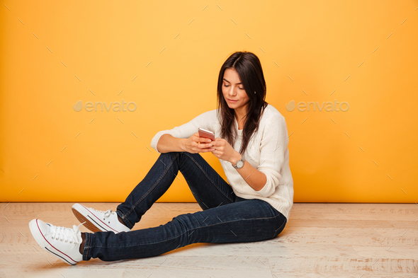 Portrait of a pretty young woman sitting on a floor - Stock Photo - Images
