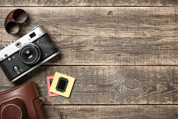 Retro camera and roll film on wooden background - Stock Photo - Images