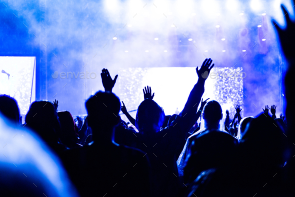 Rear view of crowd with arms outstretched at concert. Summer music festival concept - Stock Photo - Images