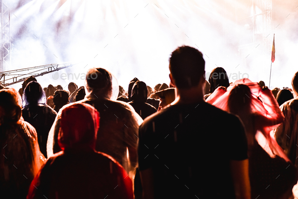 Cheering crowd of people in front of bright stage lights. Music concert - Stock Photo - Images