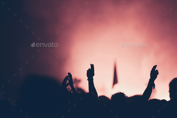 Silhouette of crowd at concert with raised arms - Stock Photo - Images