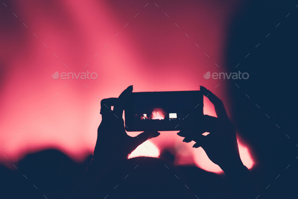 Close up of hands recording video with smart phone during a live concert - Stock Photo - Images