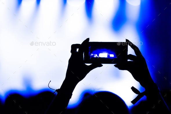 Silhouette of hands recording video with smart phone at music concert - Stock Photo - Images
