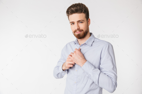 Portrait of a smiling young man buttoning - Stock Photo - Images