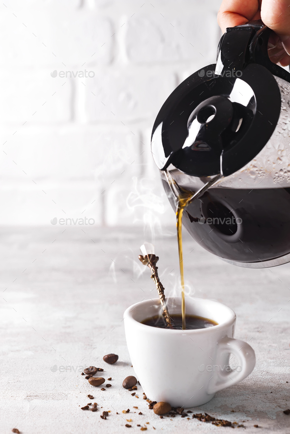 Pouring a cup of hot coffee into the glass for breakfast. - Stock Photo - Images