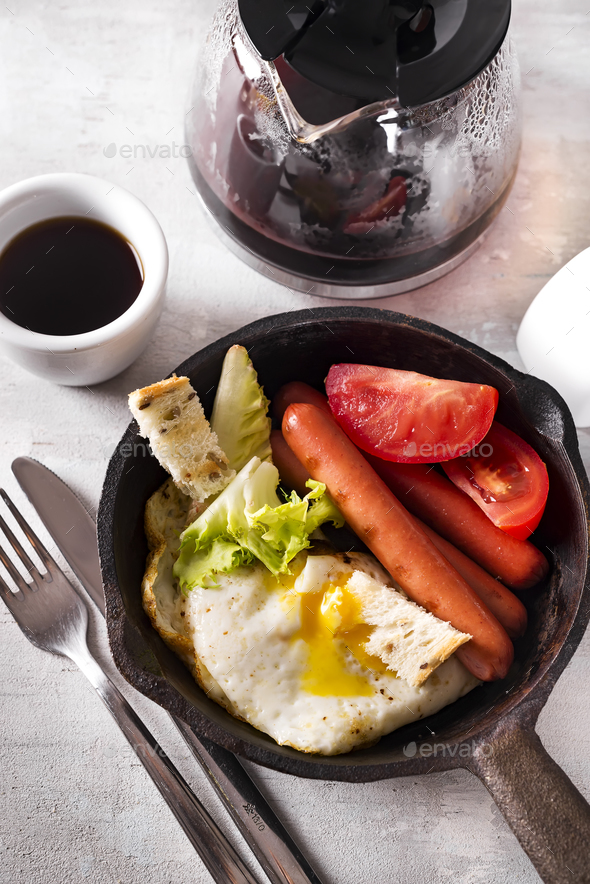 Homemade delicious american breakfast with fried egg, toast, sausage, vegetable, black coffee - Stock Photo - Images