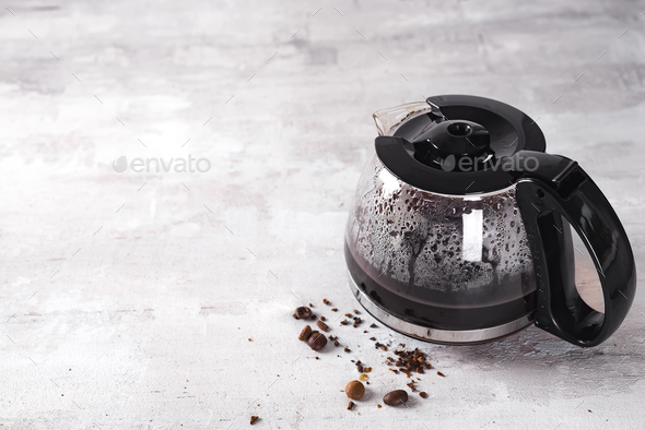 Coffee maker pot filling with coffee beans - Stock Photo - Images