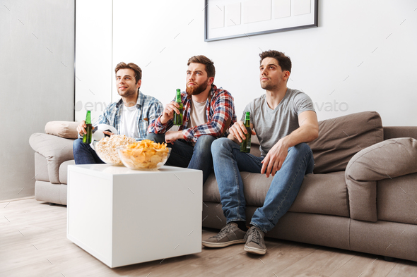 Portrait of three concentrated young men watching football - Stock Photo - Images