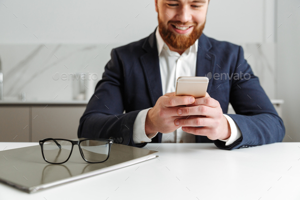 Cropped image of a happy young businessman dressed in suit - Stock Photo - Images