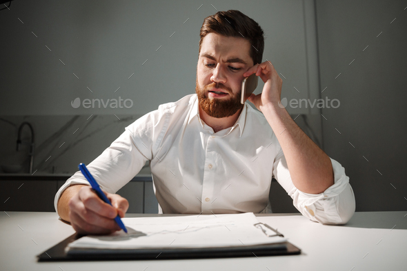Portrait of a busy young businessman - Stock Photo - Images