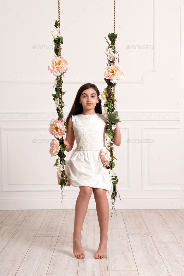 Young girl sitting on swing in bright room - Stock Photo - Images