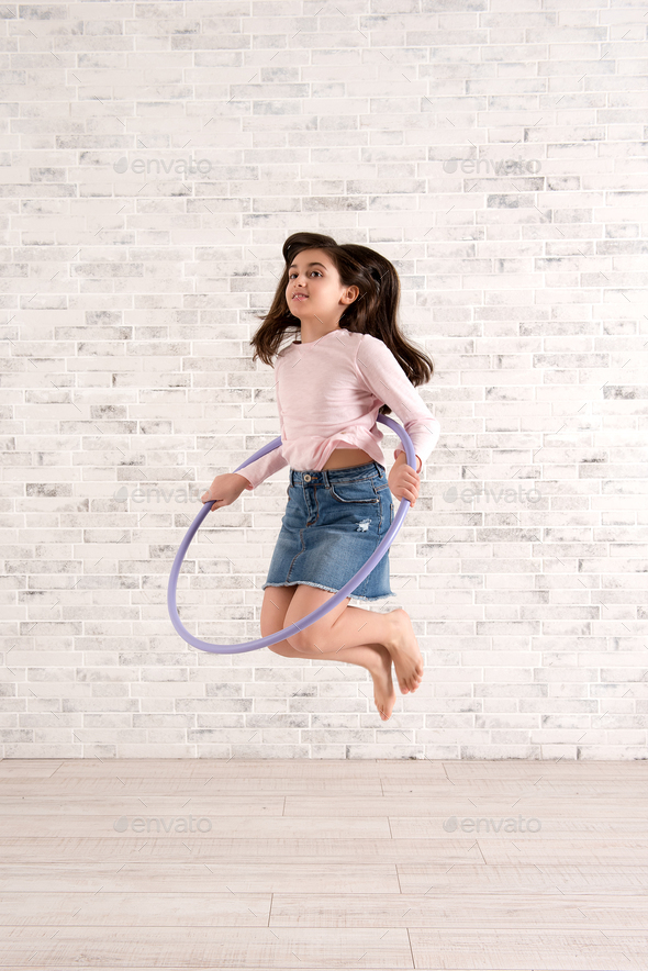 Girl playing with hula hoop in bright room - Stock Photo - Images