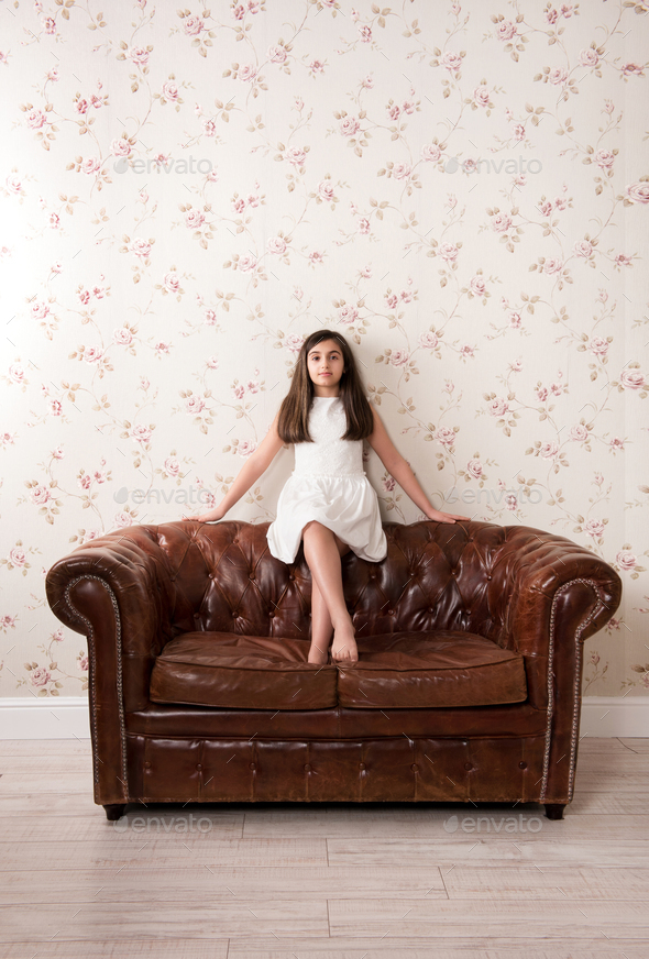 Portrait of a pretty little girl on a leather sofa - Stock Photo - Images