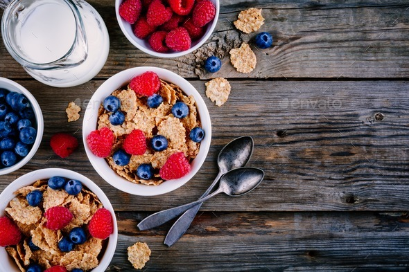 A healthy breakfast bowl. Whole grain cereal with fresh blueberries and raspberries - Stock Photo - Images
