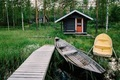 Traditional wooden hut. Finnish sauna on the lake and pier with fishing boats - PhotoDune Item for Sale