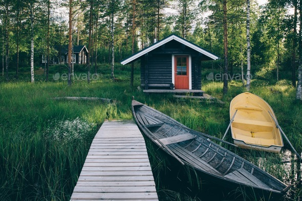 Traditional wooden hut. Finnish sauna on the lake and pier with fishing boats - Stock Photo - Images