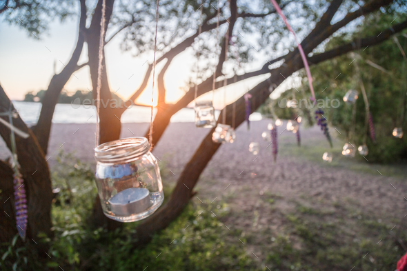 Mason jar candle hanging on tree for wedding decor - Stock Photo - Images