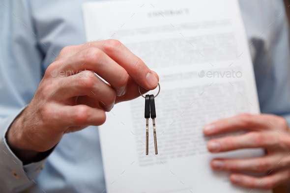 Businessman offering a key with contract. Rental agreement with contract - Stock Photo - Images