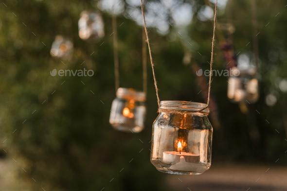 Mason jar candle hanging on tree for wedding decor - Stock Photo - Images
