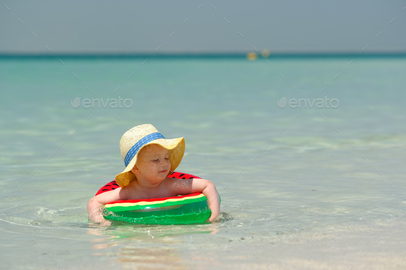 Toddler boy with swim ring on beach - Stock Photo - Images