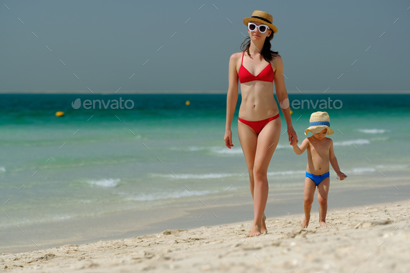 Toddler boy walking on beach with mother - Stock Photo - Images