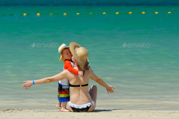 Two year old toddler boy with mother on beach - Stock Photo - Images