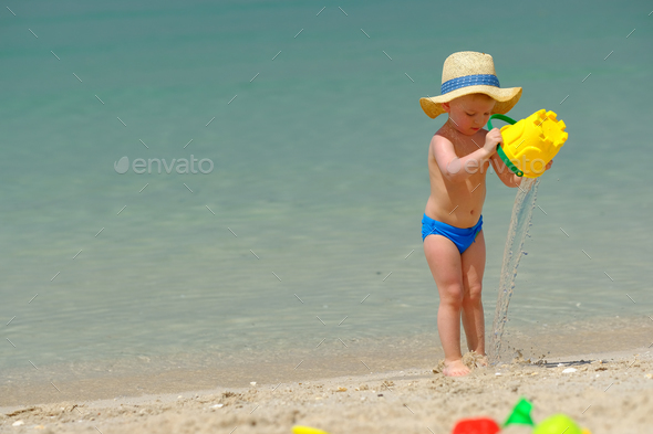 Two year old toddler playing on beach - Stock Photo - Images