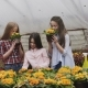 Portrait of Smiling Girls Looking and Smelling Flowers in Greenhouse - VideoHive Item for Sale