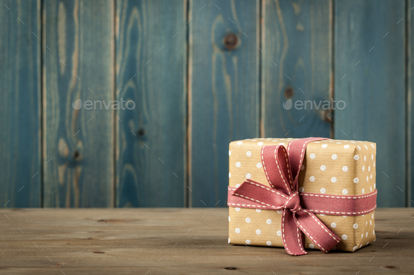 Polka dot gift box on wooden table - Stock Photo - Images