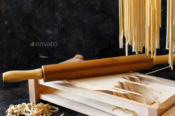 Making tagliolini pasta alla chitarra with a tool - Stock Photo - Images