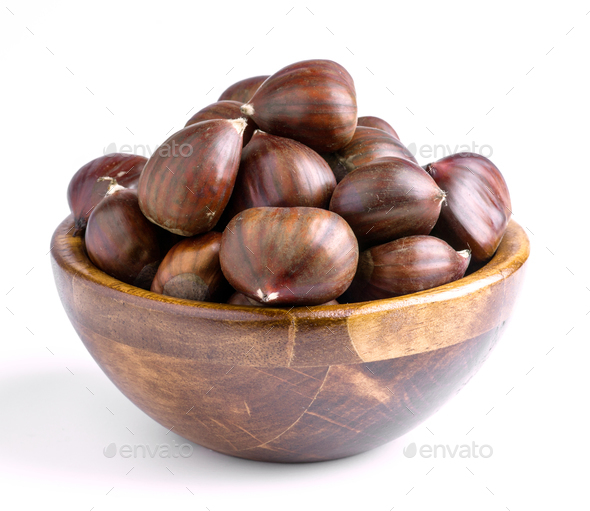 Uncooked chestnuts in wooden bowl isolated on white - Stock Photo - Images