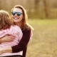 Happy Family Is Resting in a Spring Park. Mom and Daughter Are Hugging and Laughing Cheerfully - VideoHive Item for Sale