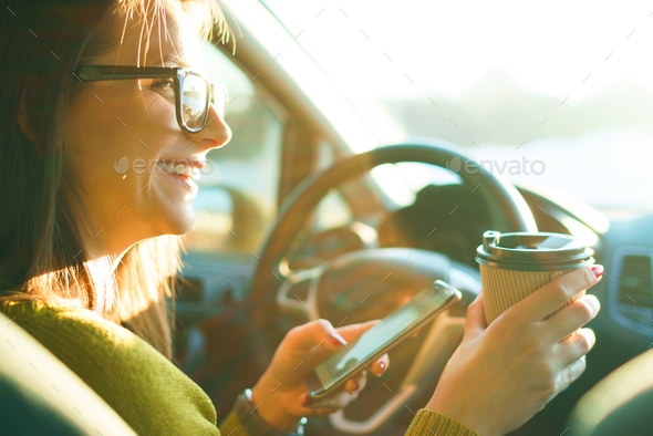Woman using smartphone and drinking coffee while sitting in a ca - Stock Photo - Images