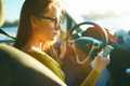 Woman in glasses uses a smartphone while driving a car at sunset - PhotoDune Item for Sale