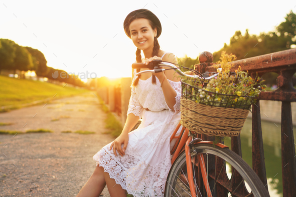 Young beautiful woman sitting on her bicycle with flowers at sun - Stock Photo - Images