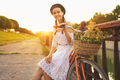 Young beautiful woman sitting on her bicycle with flowers at sun - PhotoDune Item for Sale