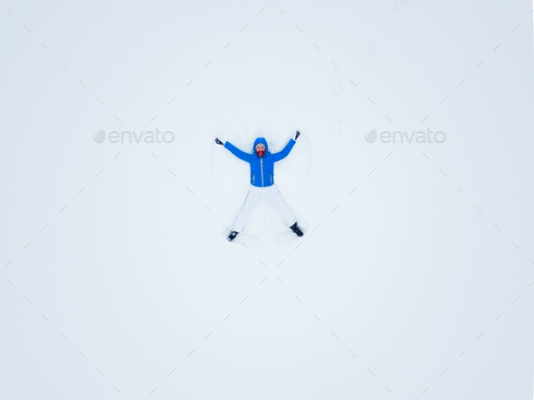 Aeriel view from the drone on woman making snow angels and playi - Stock Photo - Images