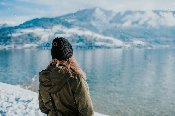 Woman standing on the lakeshore with snowy mountains in the back - Stock Photo - Images