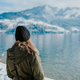 Woman standing on the lakeshore with snowy mountains in the back - PhotoDune Item for Sale