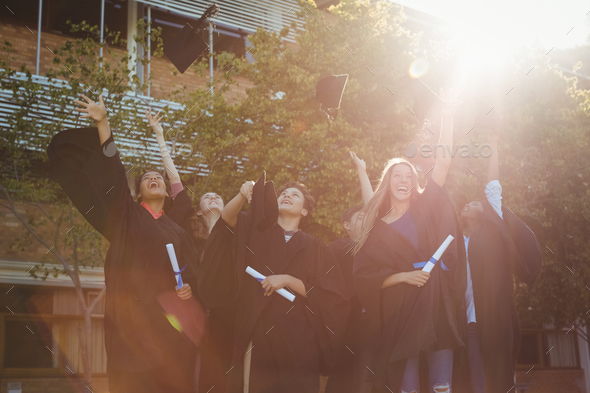 Successful graduate school kids throwing mortarboard in air in campus - Stock Photo - Images
