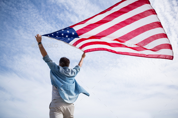 Rear view of man holding american flag on beach - Stock Photo - Images