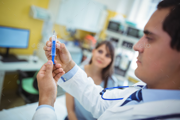 Doctor preparing a syringe to give an injection - Stock Photo - Images