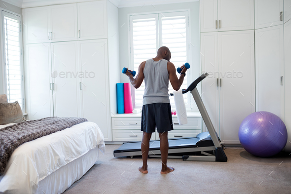 Rear view of man exercising with dumbbells in bedroom - Stock Photo - Images