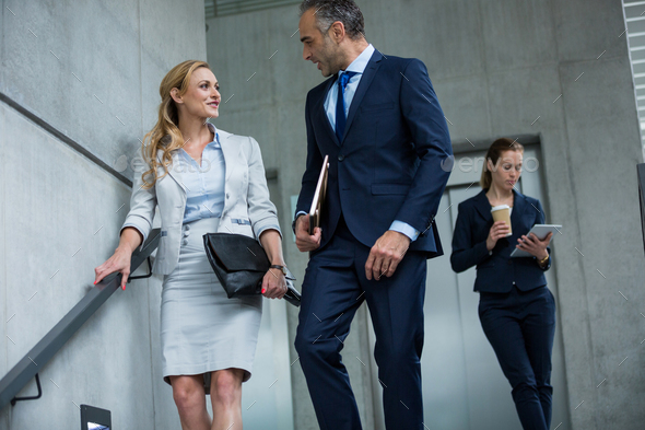 Business colleagues talking to each other while walking down stairs - Stock Photo - Images