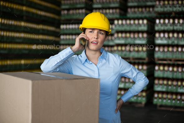 Female factory worker talking on mobile phone - Stock Photo - Images